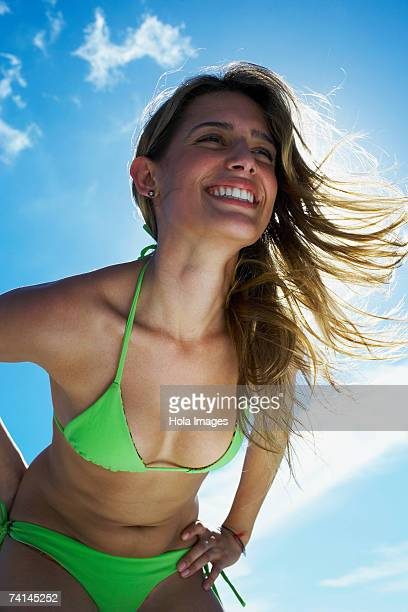 young woman smiling on beach - bend over cleavage stock photos and pictures