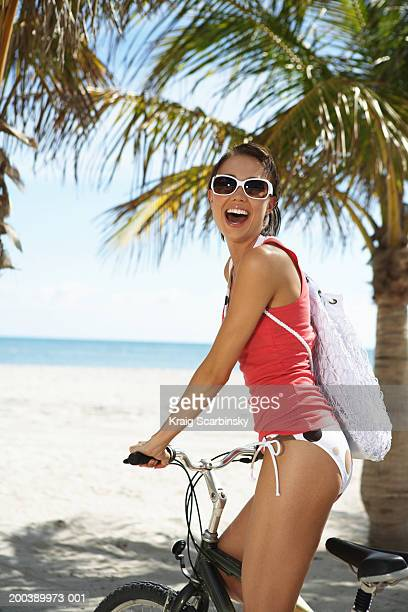 Young woman smiling on bicycle, portrait
