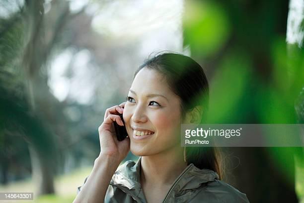 young woman smiling on phone - 歯を見せて笑う ストックフォトと画像
