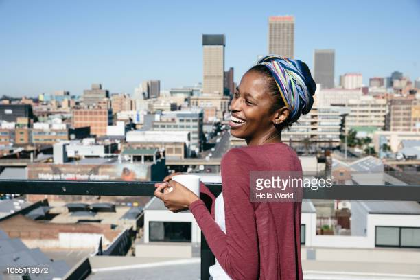 young woman smiling on rooftop while holding coffee cup - ヨハネスブルグ ストックフォトと画像