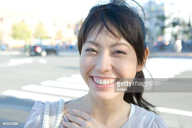 Young woman smiling on street, portrait