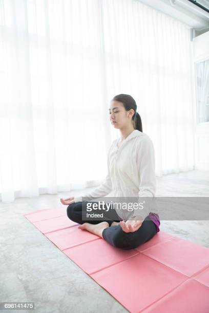Young woman smiling on yoga mat