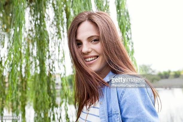 Young woman smiling outdoors, portrait