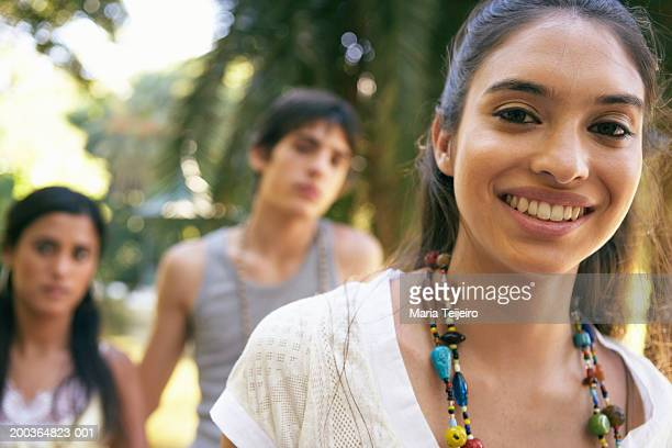 Young woman smiling, portrait, teenage couple (16-18) in background