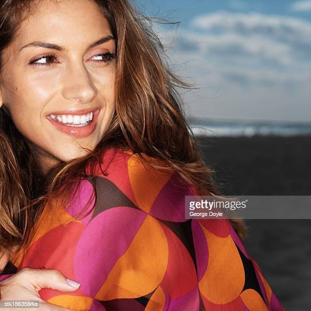 Young woman smiling sitting at the beach
