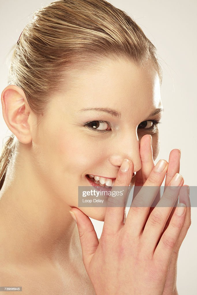 Young woman smiling, touching nose, close-up, portrait : Stock Photo