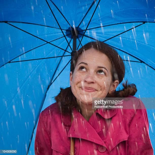 Mujer joven sonriendo bajo una sombrilla