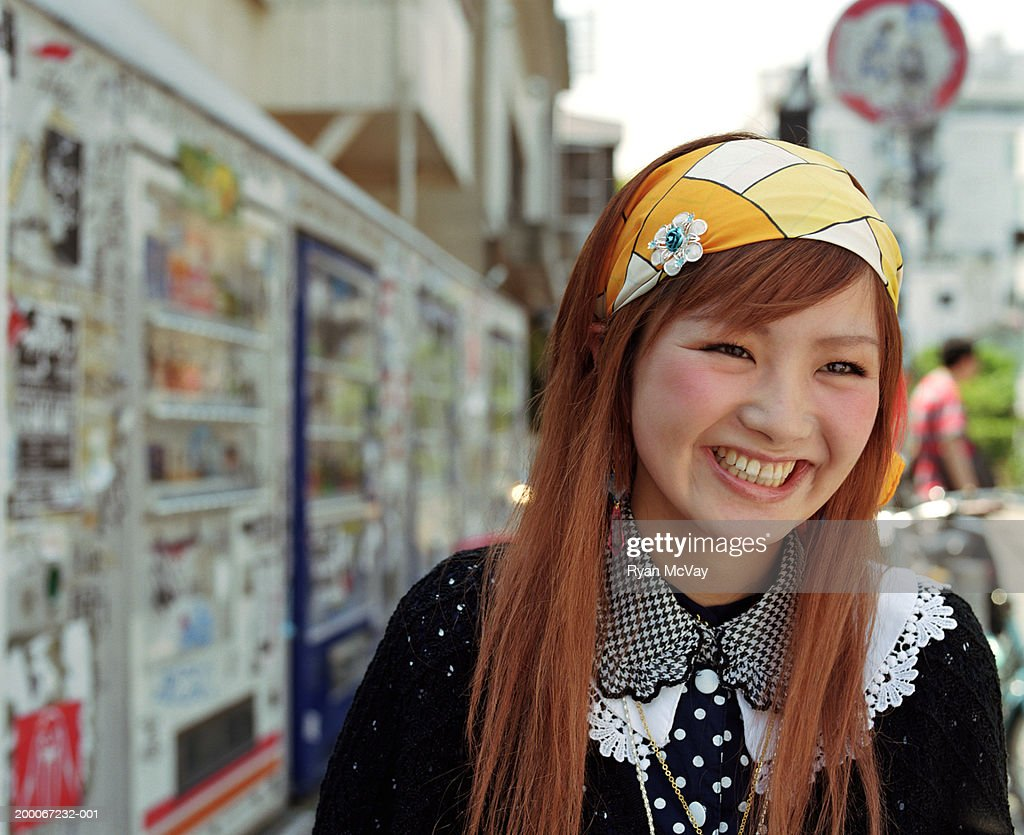Young woman smiling, urban scene in background, portrait : Stock Photo