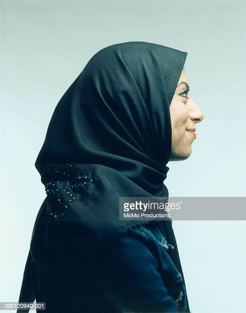 Young woman smiling, wearing head scarf, profile