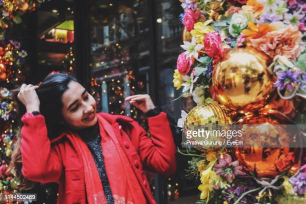 young woman smiling while looking at christmas decorations outdoors - wanchai stock photos and pictures
