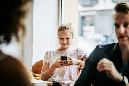 Young Woman Smiling While Messaging Friends On Smartphone In Cafe - gettyimageskorea