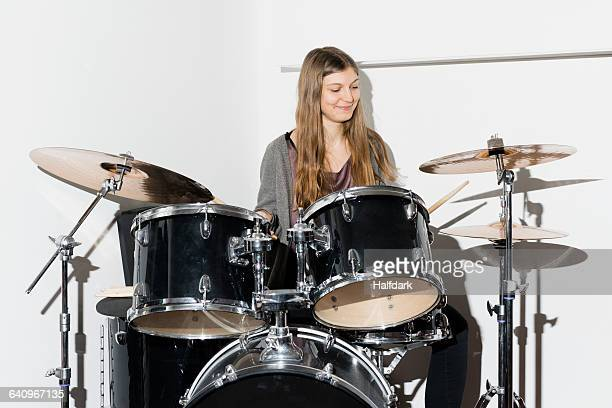Young woman smiling while playing drums