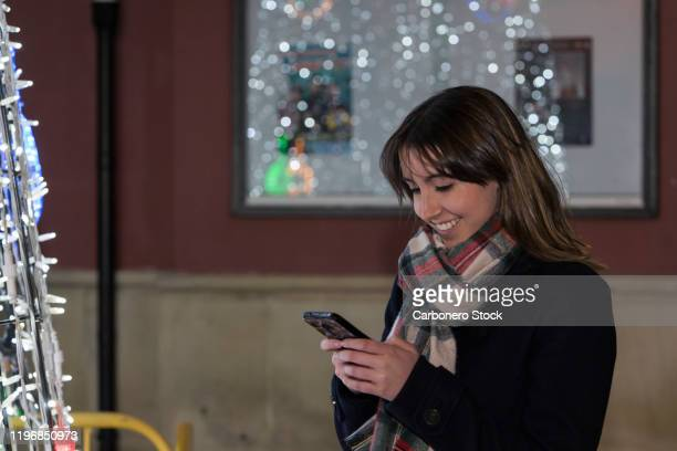 young woman smiling while reading a message on mobile - snood headwear stock photos and pictures