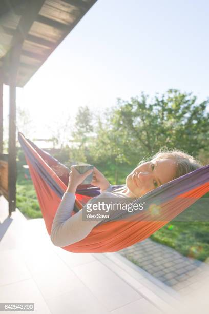 Young woman smiling while relaxing in hammock