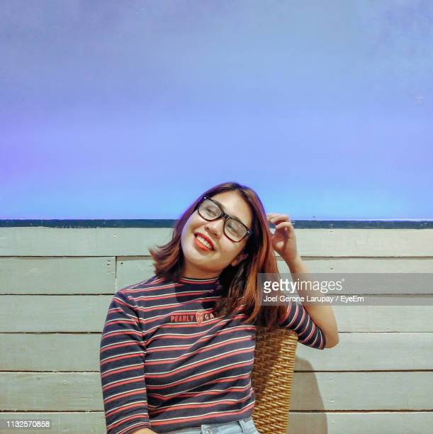 young woman smiling while sitting on seat against blue sky - filipino woman stock pictures, royalty-free photos & images