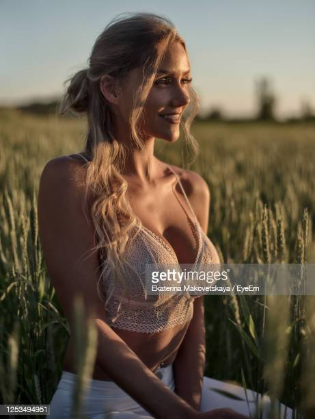 young woman smiling while standing on field - cleavage stock pictures, royalty-free photos & images