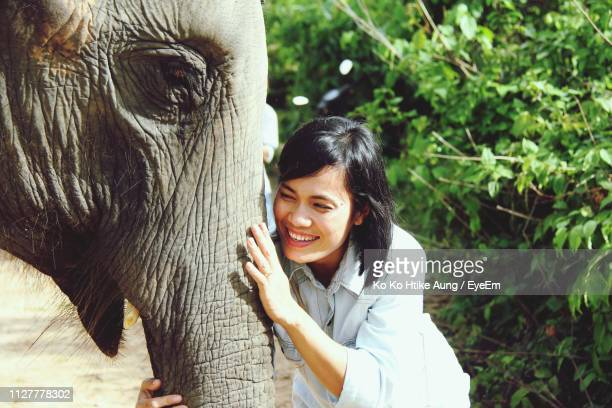 young woman smiling while touching elephant against plants - ko ko htike aung stock pictures, royalty-free photos & images