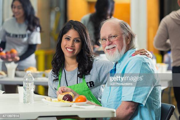 young woman smiling while volunteering with seniors at food bank - depression bread line stock pictures, royalty-free photos & images