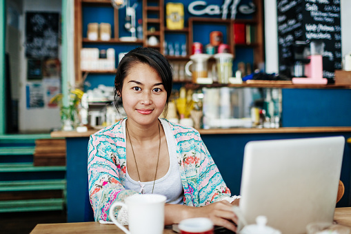 Young Woman Smiling While Working On Laptop In Colourful Coffee Shop - gettyimageskorea