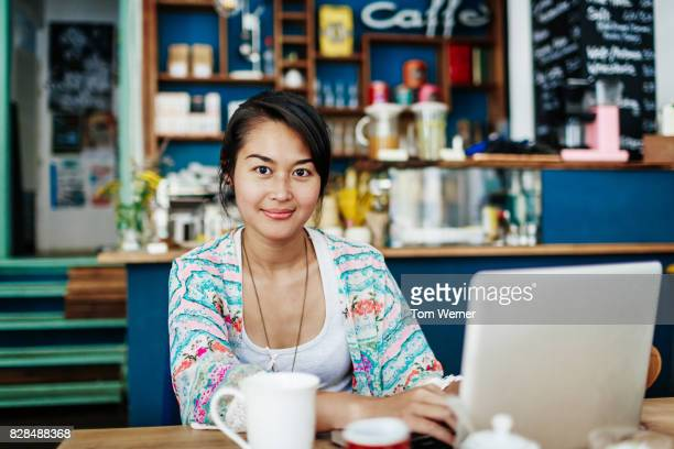 Young Woman Smiling While Working On Laptop In Colourful Coffee Shop
