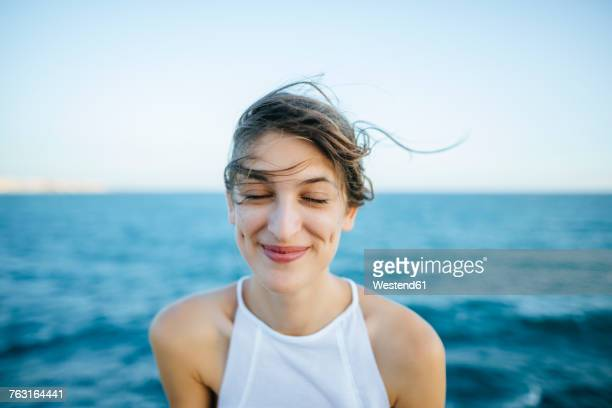 young woman smiling with eyes closed with sea background - contented emotion stock pictures, royalty-free photos & images