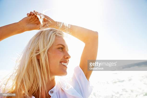 young woman smiling with hands over head on beach - blonde hair stock pictures, royalty-free photos & images