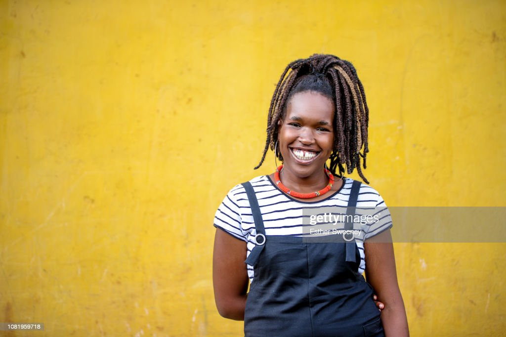 Young woman smiling with yellow background : Stock-Foto