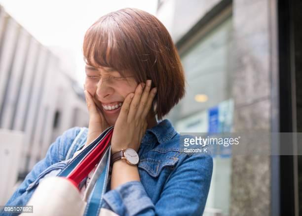 頬に手を持つ若い女性 smilying - 恥ずかしがり ストックフォトと画像