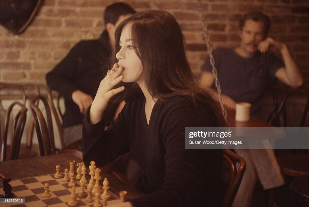 A young woman smokes a cigarette as she plays chess in a