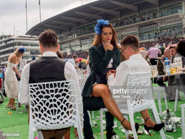 A young woman smokes a cigarette straddled across a man's lap on Ladies' Day at Epsom Ladies' Day is traditionally held on the first Friday of June a...