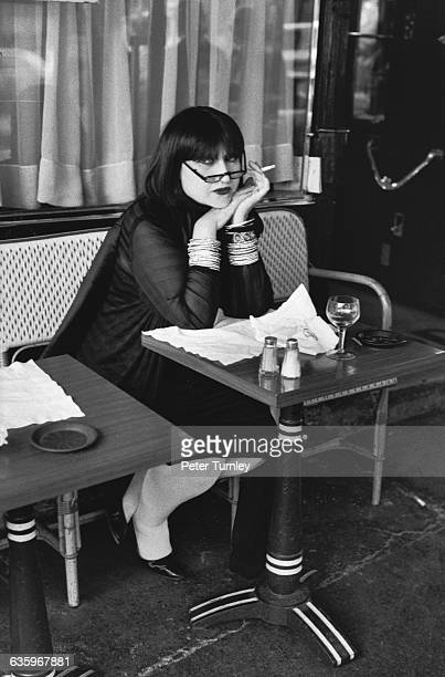 A young woman smokes at her table in the Brasserie Lipp
