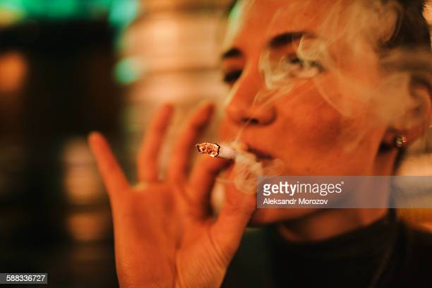 Young woman smoking a cigarette in a bar