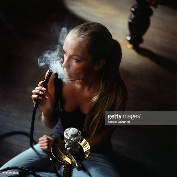 young woman smoking a hookah - chicha photos et images de collection