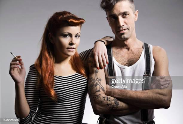 Junge Frau Rauchen und Schiefer auf Mann mit Tätowierungen