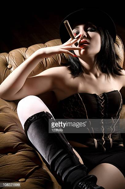 young woman smoking cigar  and wearing lingerie on leather couch - jarretel stockfoto's en -beelden