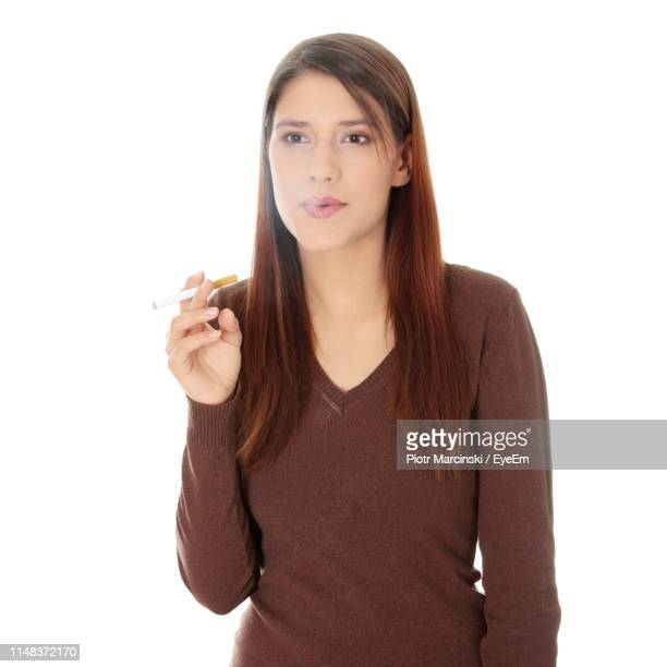 young woman smoking cigarette against white background - beautiful women smoking cigarettes stock pictures, royalty-free photos & images