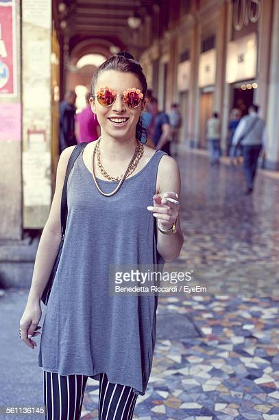 Young Woman Smoking Cigarette And Smiling At Market