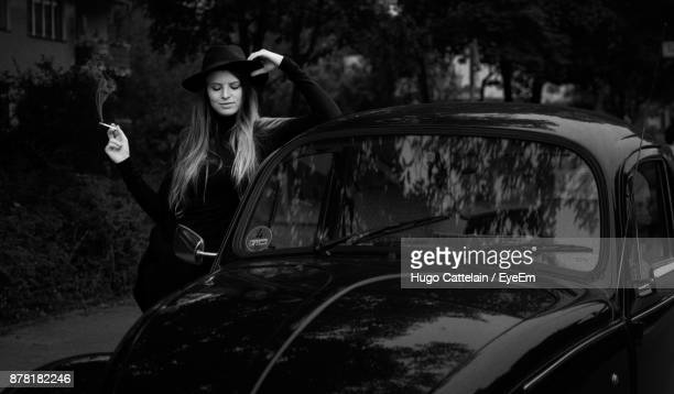 Young Woman Smoking Cigarette By Car