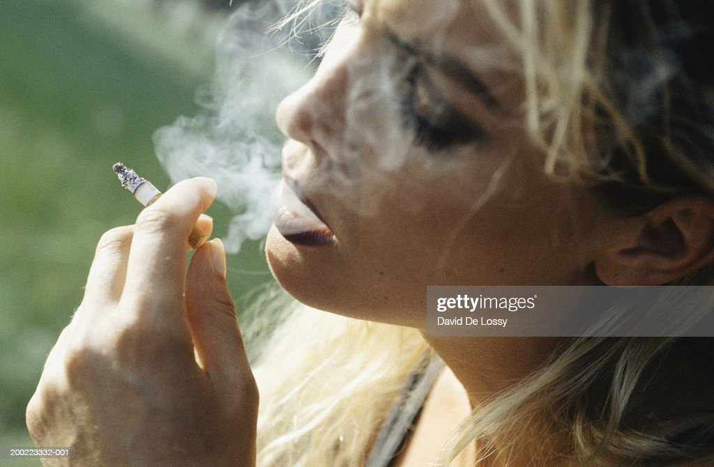 Young woman smoking cigarette, close-up : Stock Photo
