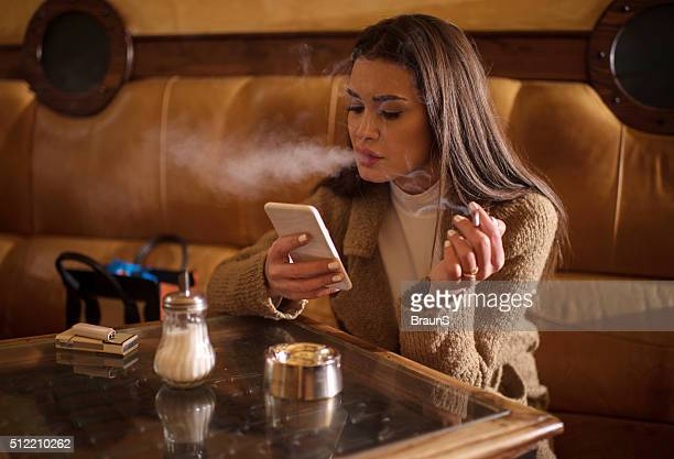 Young woman smoking in a cafe while using cell phone.