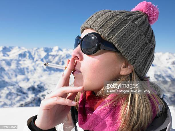 Young woman smoking in snow gear