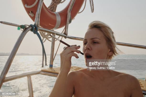 Young Woman Smoking On Boat In Sea During Sunset