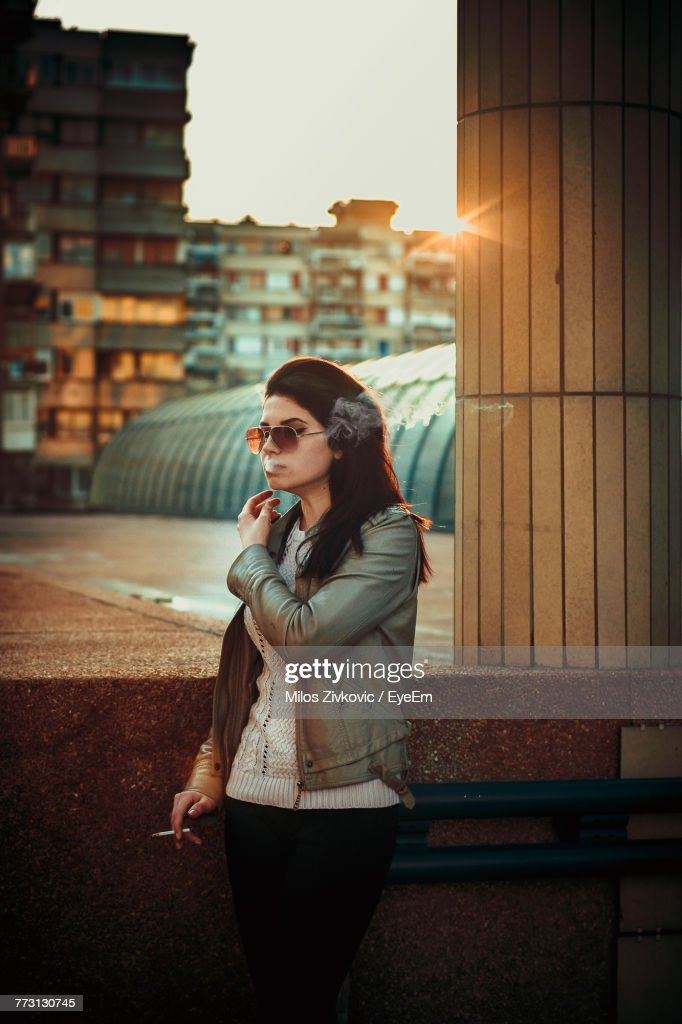 Young Woman Smoking While Standing On Street In City : Photo