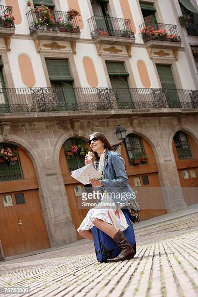 Young Woman Snacking While Reading Map