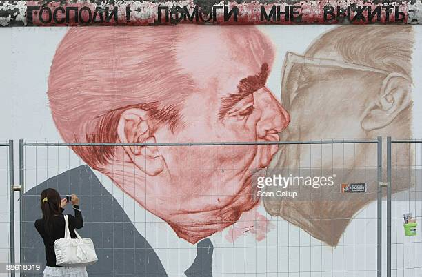 A young woman snaps a picture of the work in progress by Russian artist Dmitry Vrubel showing former Soviet leader Leonid Brezhnev kissing former...