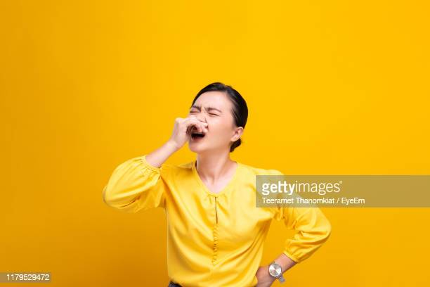 young woman sneezing against yellow background - くしゃみ ストックフォトと画像