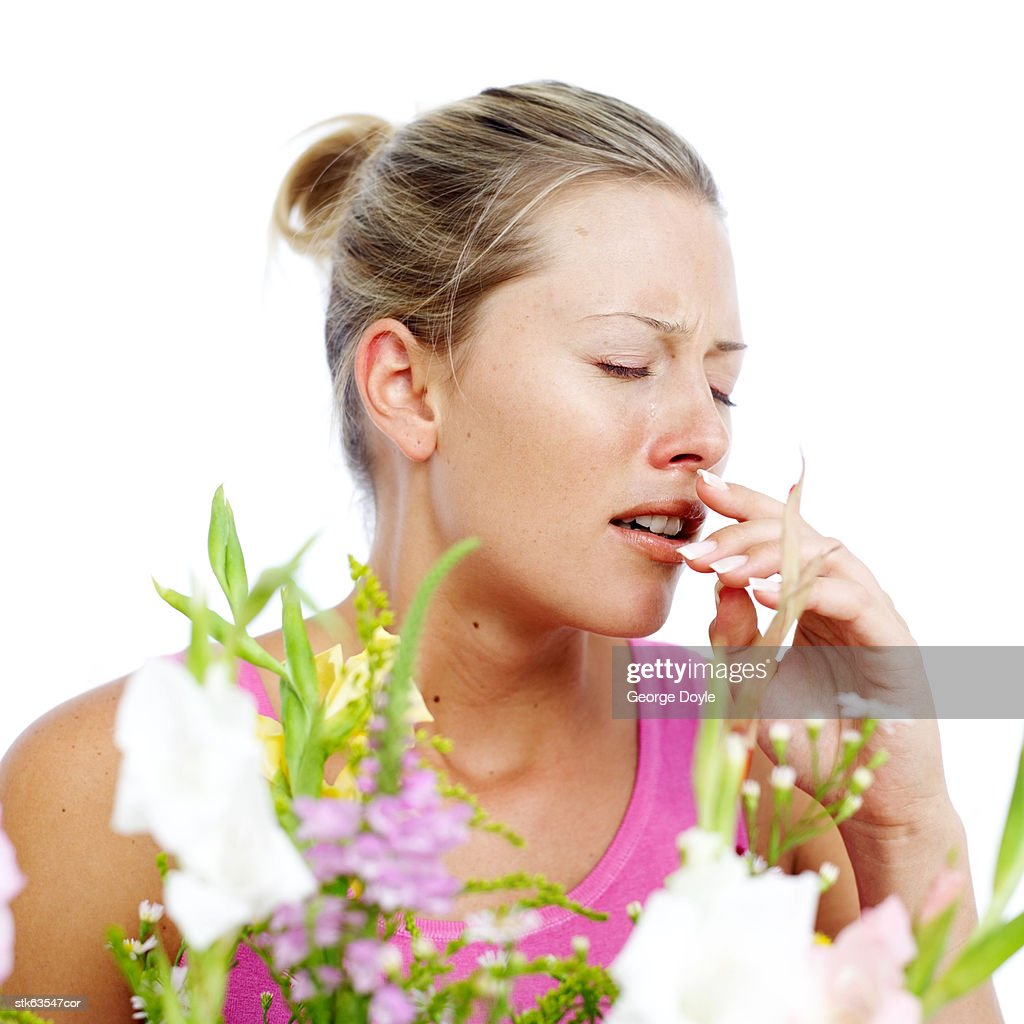 young woman sneezing due to pollen dust from flowers : Stock Photo