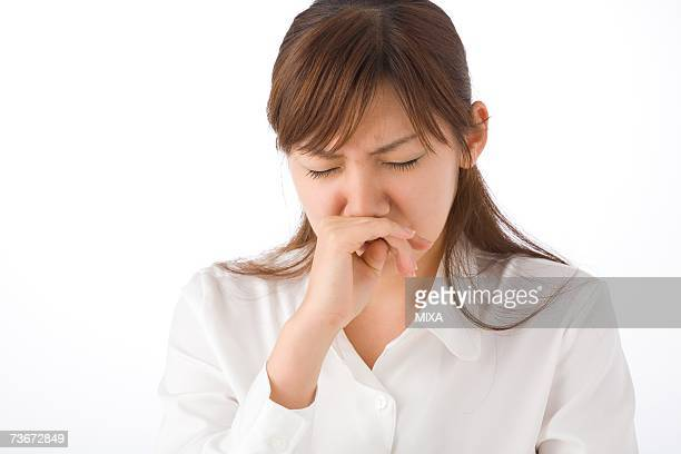 A young woman sneezing
