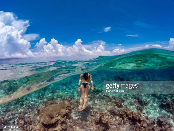 young woman snorkeling in ocean - undersea stock photos and pictures
