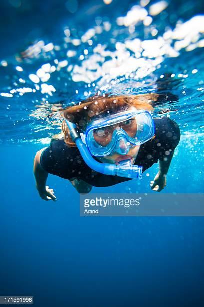 Mujer joven haciendo esnórquel submarino